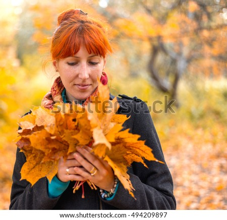 The girl walks in autumn forest with leaves