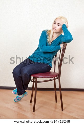 The girl was asleep sitting on a chair