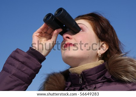 The girl was surprised to look through binoculars, the background sky - stock photo