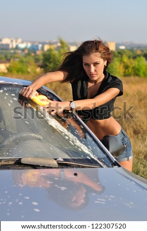 The girl washes the car outdoor - stock photo
