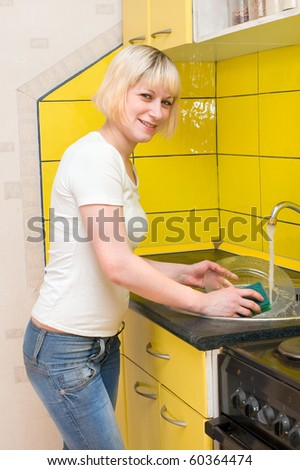 The girl washes ware on kitchen