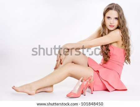 The girl wears a shoe, white background - stock photo