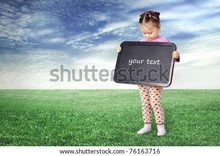 The girl with a board for drawing on a meadow