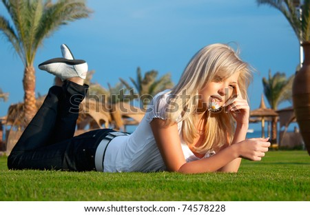 The girl with a camomile lies on a grass - stock photo