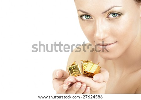 The girl with a golden skin stretches three golden gifts in a hand - stock photo