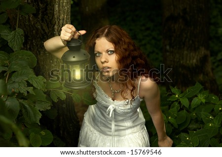 The girl with a lantern restlessly looks on a background of a twilight wood