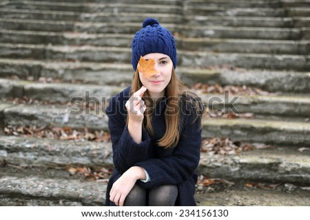 the girl with a maple leaf sits on steps in city park - stock photo