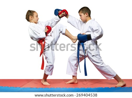 The girl with a red belt kicks the boy with a blue belt - stock photo