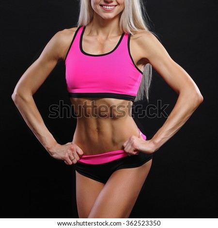 The girl with a sports body. On a black background - stock photo
