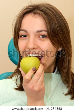 The girl with an apple in the dental office