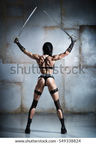 The girl with an athletic physique, in an unusual dress, with swords in their hands, shows a beautiful back