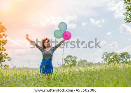 The girl with balloons plays in a field with sunshine