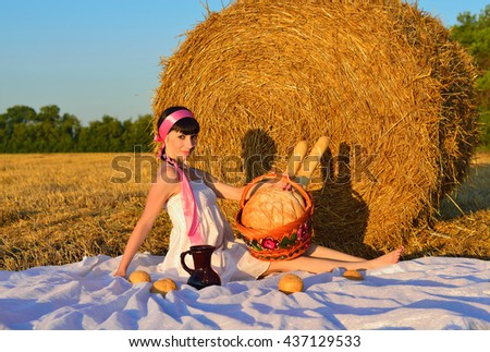 The girl with bread, a long loaf and milk on a mow