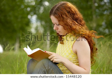 The girl with enthusiasm reads the book in park - stock photo