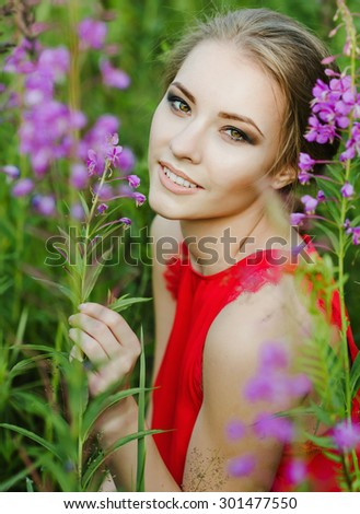 the girl with flowers in the field - stock photo