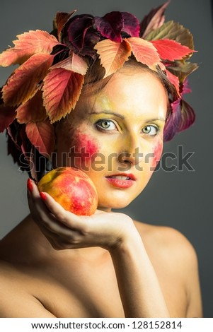The girl with hair of autumn leaves, berries and fruit. - stock photo