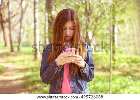 The girl with long straight brown hair in a denim jacket with a phone in his hand in the park against the backdrop of tall trees and greenery