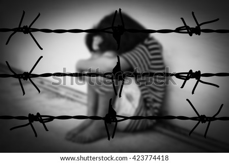 the girl with lower head on her knee sitting beside wall in white tone with silhouette of barbed fence and shadow edge - stock photo