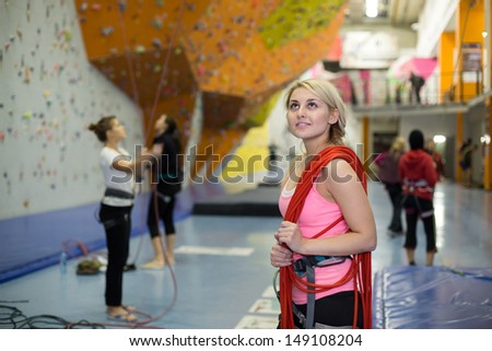 The girl with rope on shoulder on the climbing gym - stock photo