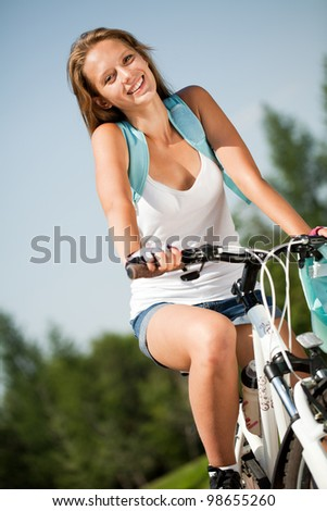 the girl with the bike in the park on a summer day