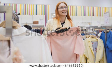 The girl with the glasses is buying a pink dress in women's clothing store