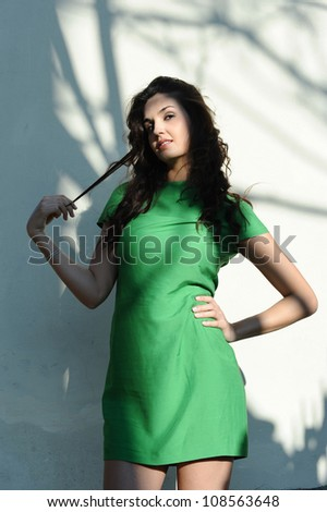 the girl with the green dress smiles with sensuality - stock photo