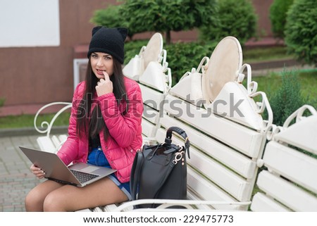 the girl with the laptop sits on a bench and slipped a finger into her mouth