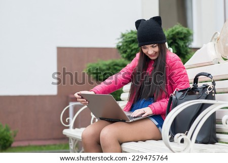 the girl with the laptop sits on a bench and smiling