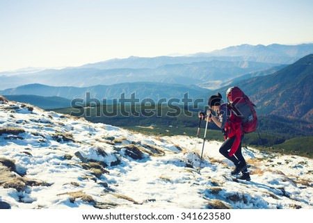 The girl with the rucksack moves along a mountain trail. - stock photo