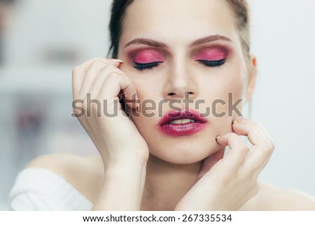 The girl with the smeared lipstick and closed eyes. Studio portrait. - stock photo