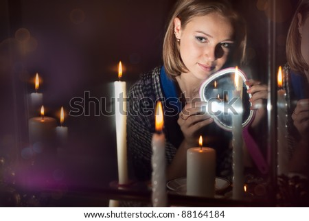 The girl wonders with a mirror in a dark room - stock photo