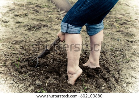 The girl working in the garden, on the ground. In the hands holding the hayfork. The girl dressed in jeans, feet without shoes, barefoot.