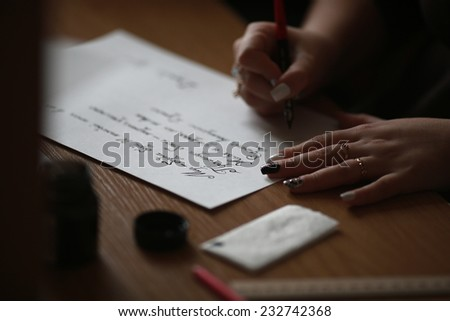 The girl writes a letter with pen and ink - stock photo
