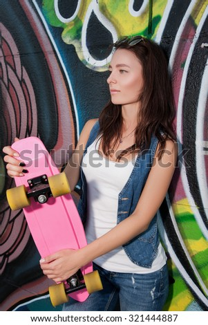 The girls on skateboards. Slim and beautiful woman holding a pink skate. Attractive girl in jeans and shirt holds the skate. Stylish girl goes in for sports and fun riding on a skateboard