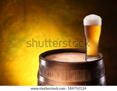 The glass of beer over woden barrel on the golden background. - stock photo