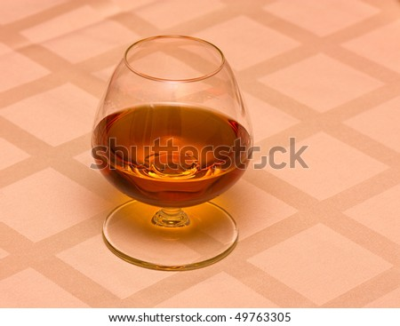The glass of cognac on the table. - stock photo
