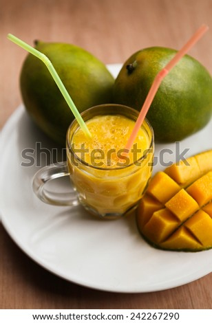 The glass of fresh mango smoothie with ripe mangoes on the white plate - stock photo