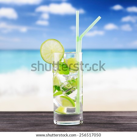 The glass of refreshing mojito cocktail containing lime slices, mint leaves and pieces of ice on a beach. Thirst-quenching drink at summer for a beach party and for relaxing on a beach - stock photo