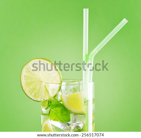 The glass of refreshing mojito cocktail containing lime slices, mint leaves and pieces of ice on a pastel green background. Thirst-quenching drink at summer for a party and for relaxing on a beach. - stock photo