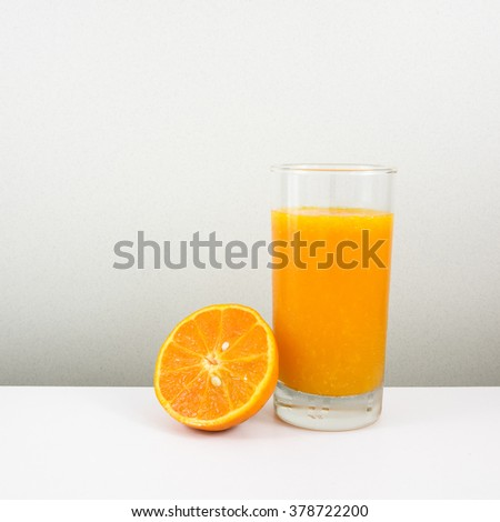 The glass of tasty pure orange juice and fresh orange half for a good healthy.