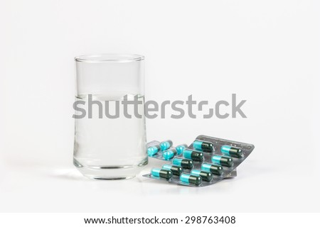 The Glass of water and medicine capsule on white background - stock photo