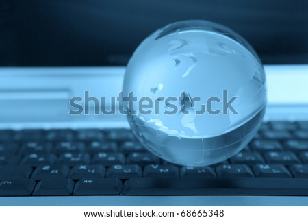 The glass sphere of a planet lies on the computer keyboard