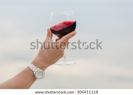 The glass with old red wine in sommelier's hand. Red wine is tasted by sommelier isolated on blue sky background. - stock photo