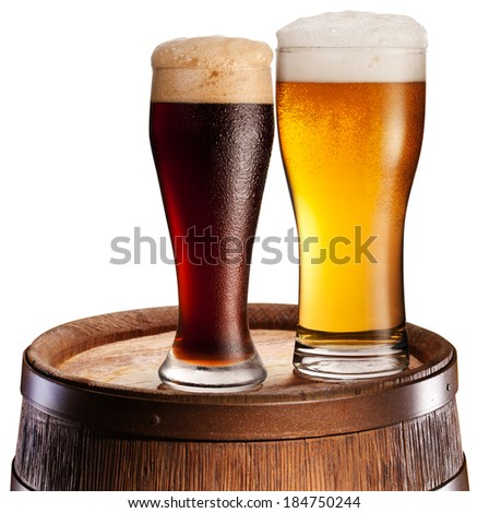 The glasses of beer over woden barrel. File contains clipping paths. - stock photo