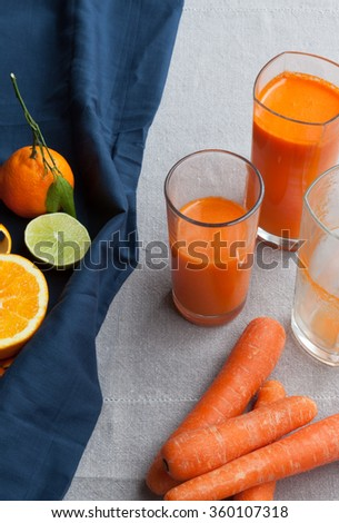The glasses of fresh carrot citrus juice with citrus fruits and carrot on the tablecloth