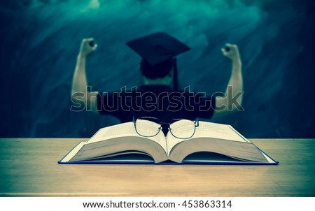 The glasses over the Books on the desk in class room with black board background,Education concept, vintage color tone - stock photo