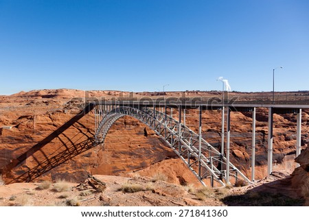 The Glen Canyon Dam Bridge arching across the red rock above the Colorado River in Page, Arizona. - stock photo