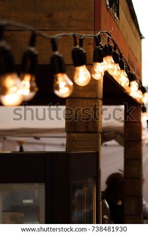 The glowing light bulbs on a black rope on a wooden facade