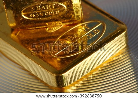 The gold bar put on the gross and shiny surface background represent gold and business finance concept related idea.