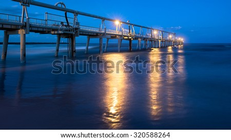 The Gold Coast Iconic Jetty With Glowing Lights Reflecting In The Ocean During Twilight, The Spit, Philip Park, Main Beach, Queensland, Australia - stock photo